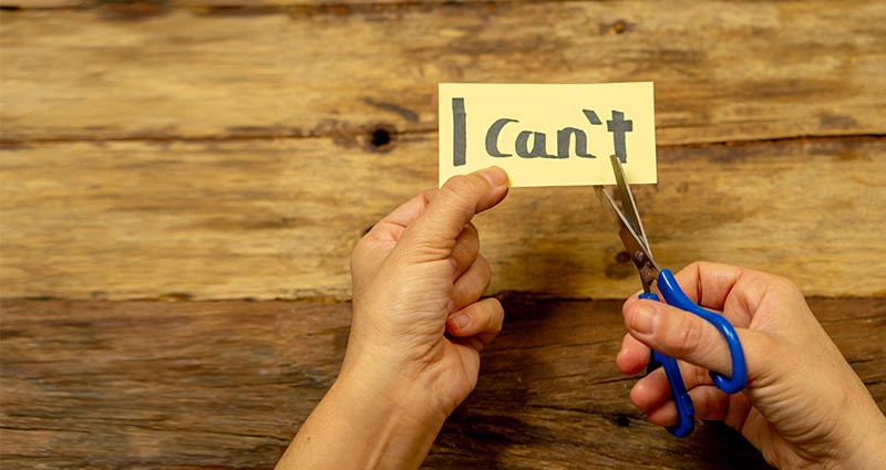 "person cutting paper that says ""I can't"""