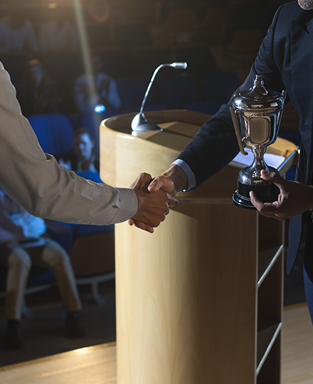 Two Men Shaking Hands At An Awards Ceremony